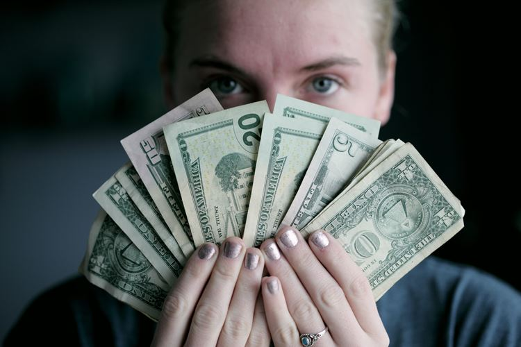 woman holding various bills in US currency