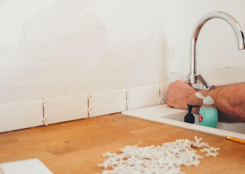 Man installing tiles behind a chrome faucet
