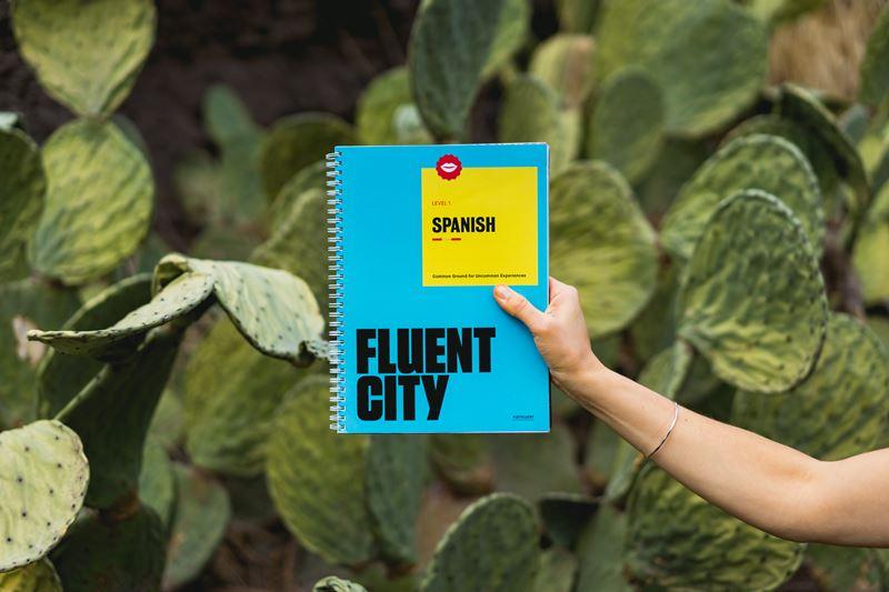 Person holding Fluent City spanish book