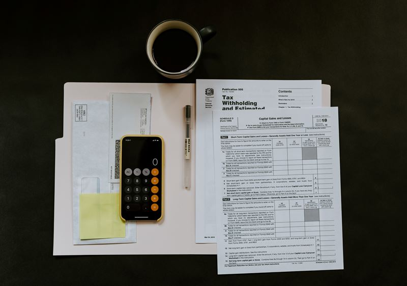 Calculator resting on a folder with tax forms