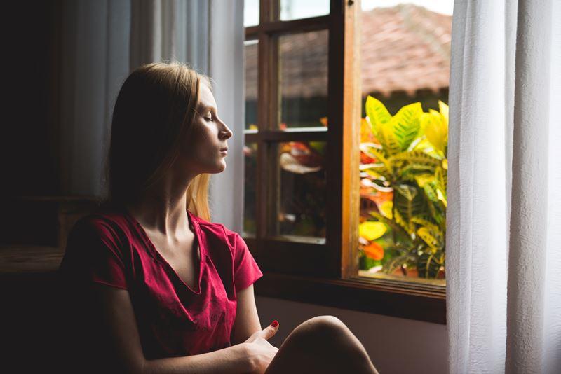 Woman sitting near an open window
