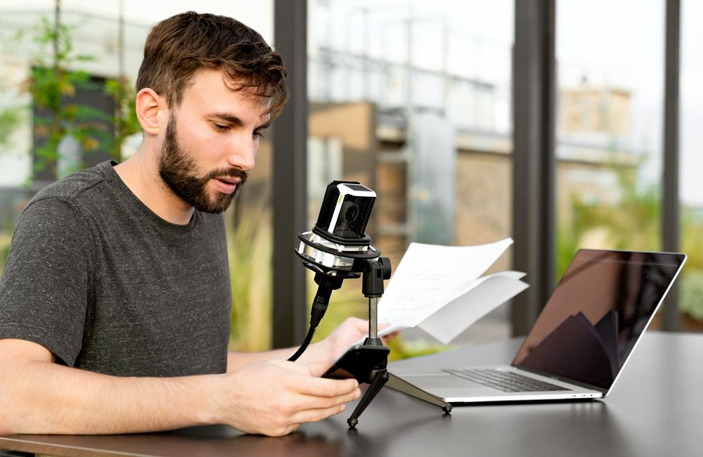 man recording script on mic in front of computer